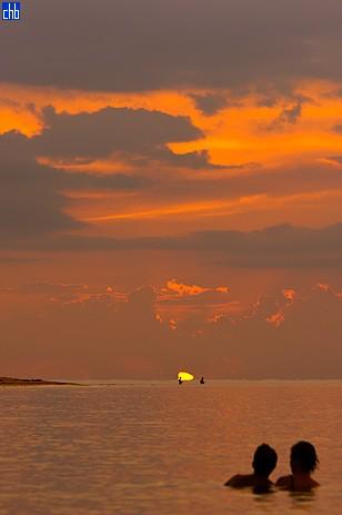 Пара туристов наблюдает за местными рыбаками на фоне заката