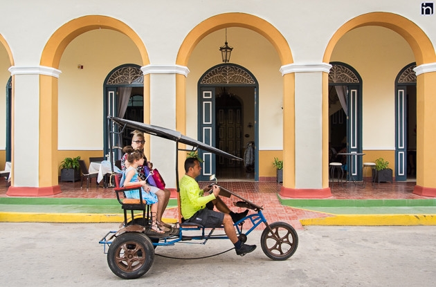 Bicitaxi passing in front of the Entrance of the Hotel Encanto Real